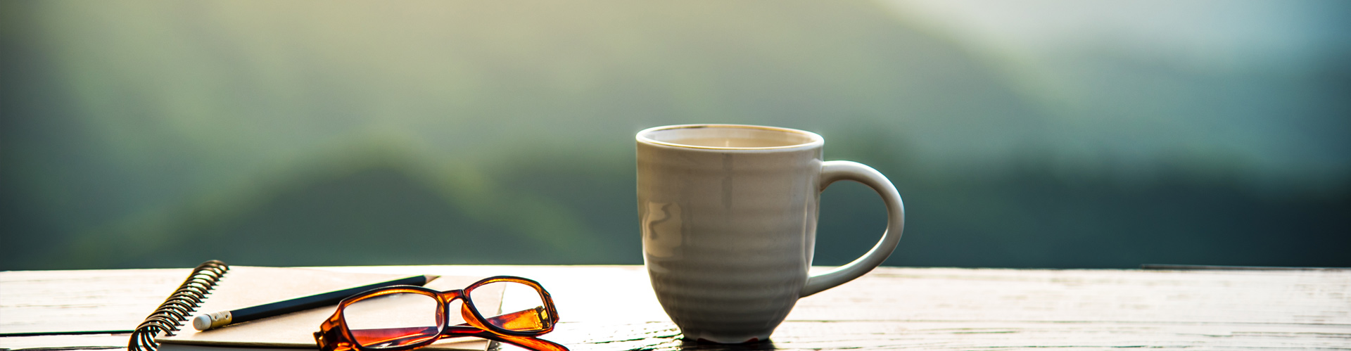 A close-up of a coffee mug, notepad, pencil and glasses resting on a wooden table outdoors