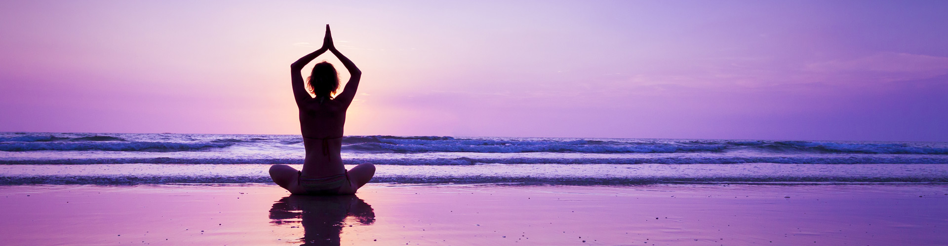 A woman doing yoga on the beach as dusk