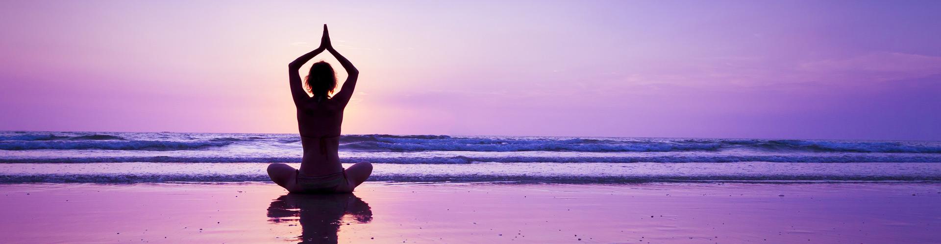 A woman doing yoga on the beach as dusk